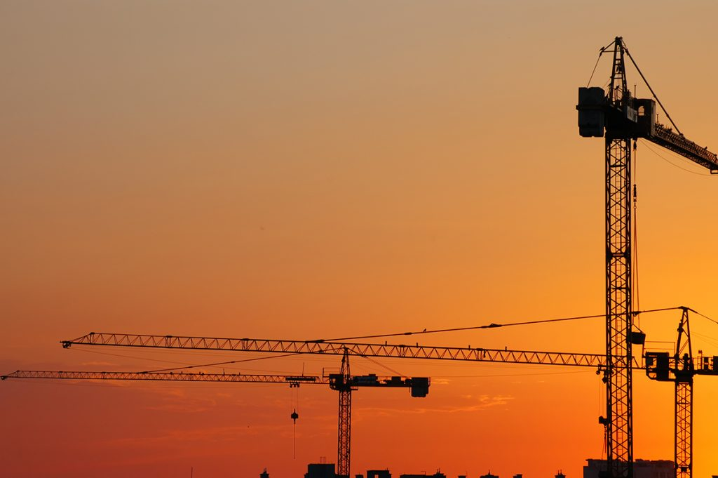 Construction cranes in the sunset